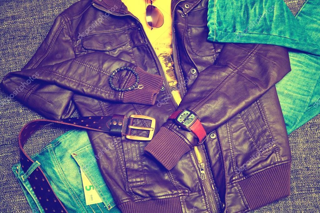 Clothing items and accessories: blue jeans with a leather belt, leather jacket, T-shirt, watches, sunglasses and a bracelet on a hand