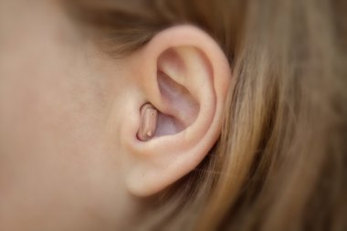Hearing aid in your ear close-up. Modern equipment in medicine