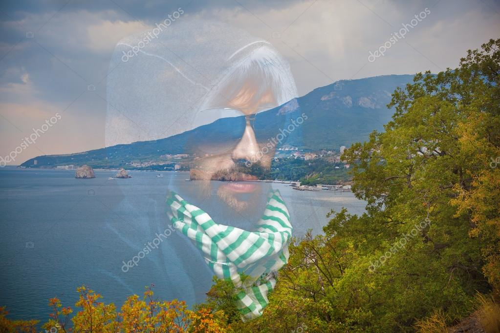 Portrait of a man in the hood, neck scarf and sunglasses. Summer landscape - sea, mountains and trees. Apply effect of double exposure.