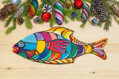 Wooden board in the form of fish. Christmas background. Christmas tree with pine cones, Christmas decorations