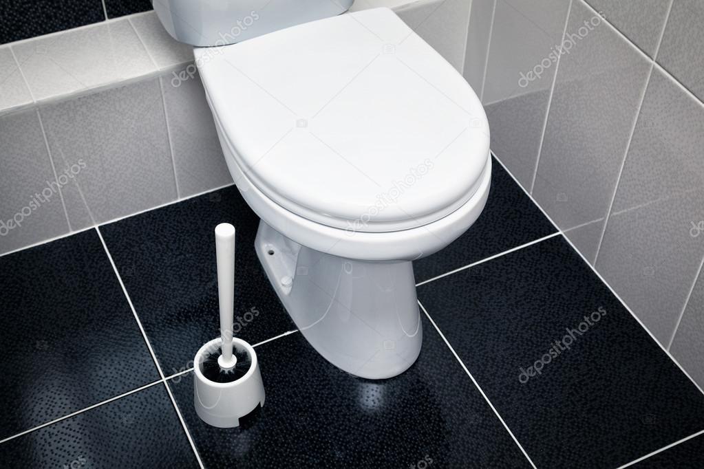 Witte wc zwarte tegels op de vloer u stockfoto devin pavel