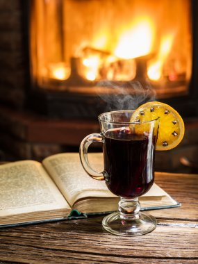 Hot mulled wine and a book on the wooden table. Fireplace with warm fire on the background. stock vector