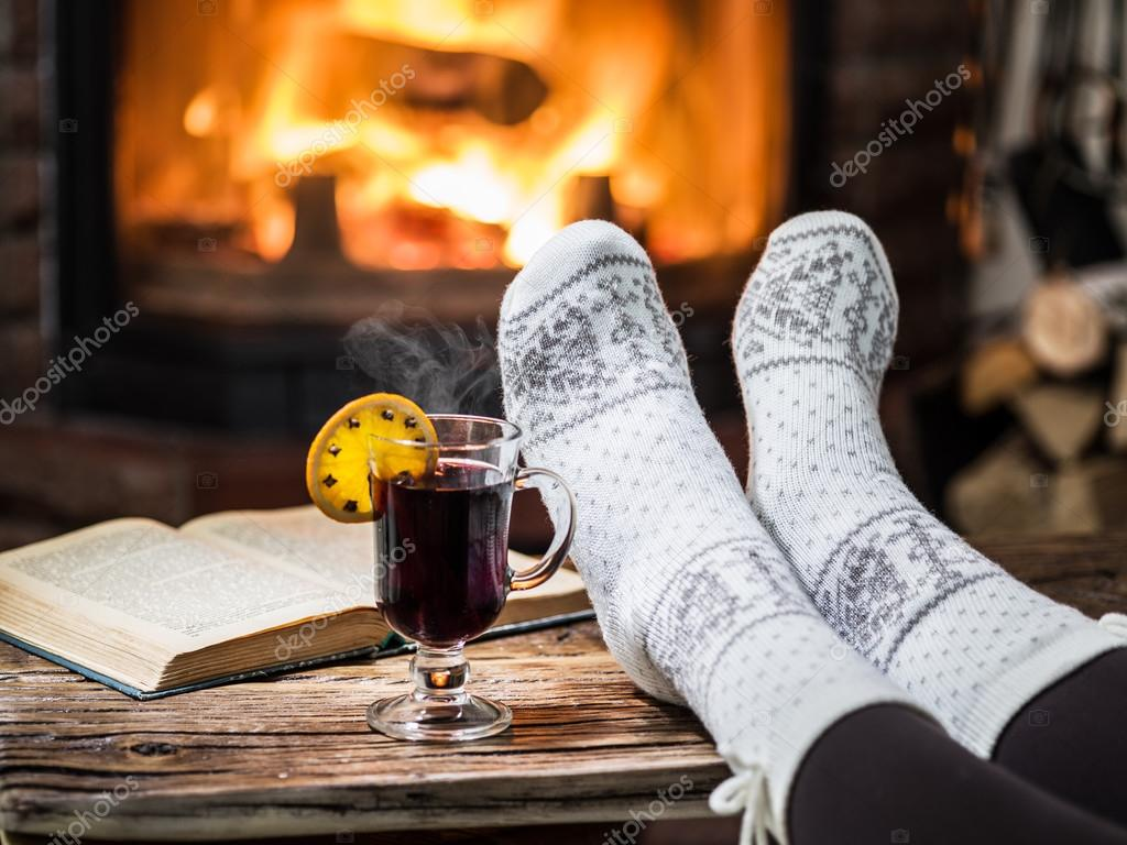 Warming and relaxing near fireplace with a cup of hot wine