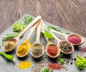 Fotografie Assortment of colorful spices in the wooden spoons.