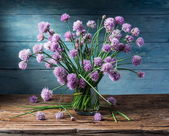 Fotografie Bouquet of onion (chives) flowers in the vase on the wooden tabl