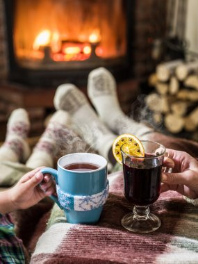 Warming and relaxing near fireplace with a cup of hot drink.