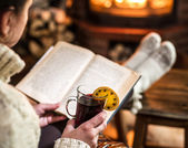 Glühwein und Buch in Frauenhand. Entspannung vor dem Fernseher