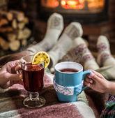Fotografie Erwärmen und Entspannen am Kamin mit einer Tasse Heißgetränk.