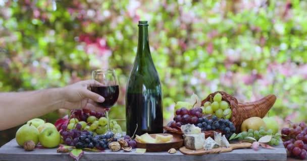 Zátiší s vínem, různými hrozny a podzimním ovocem, sýry na pozadí podzimního listí s krásným bokeh. Mužská ruka dá sklenici vína.