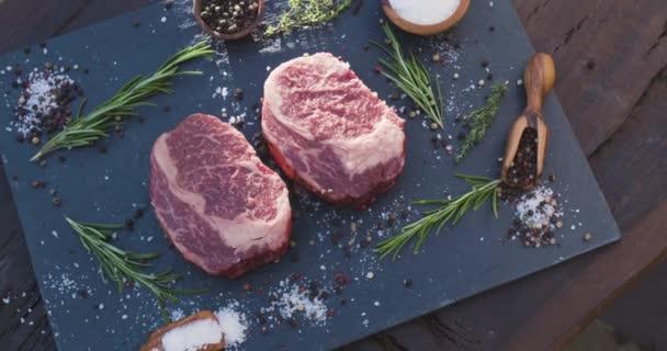 Zwei rohe Rippenaugensteaks mit Gewürzen und Kräutern auf einer Steinoberfläche. Die Kamera dreht sich langsam um die Steaks.