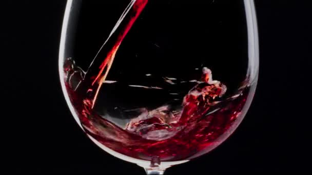 Red wine is pouring into a glass on a black background. Close shot.