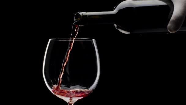 Červené víno se nalévá do sklenice na černém pozadí. Zavřít snímek.