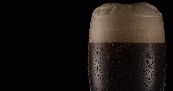 Sklenice černého piva na černém pozadí. Pivo se houpe ve skle, bubliny a pěna stoupají. Sklenice piva se pomalu otáčí ve směru hodinových ručiček.