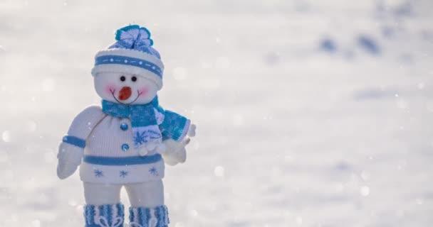 Játék vicces hóember áll a hóban egy napos téli napon, havazik.