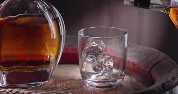 Ein Eiswürfel fällt langsam in ein Glas, steht auf einem Vintage-Fass Whisky, Whisky aus der Flasche wird sofort in das Glas gegossen. In der Nähe steht ein Dekanter mit einem Getränk vor dunkelbraunem Hintergrund. Blackmagic Ursa Pro G2.