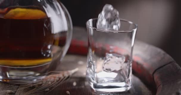 Egy jégkocka lassan beleesik egy pohárba, egy évjáratú whiskey-hordón állva, az üvegből azonnal whiskyt öntenek az üvegbe. Egy korsó ital áll a közelben, sötét barna háttér. Fekete mágia Ursa Pro G2.
