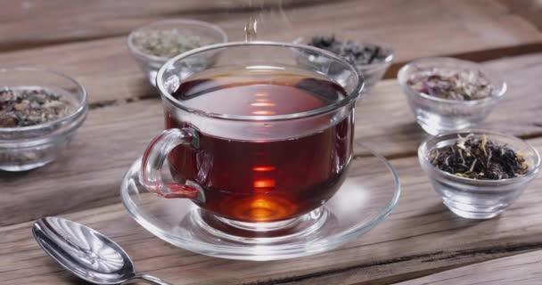 Kapka pomalu padá do skleněného šálku čaje. Kolem jsou malé misky s různými druhy listového čaje. Klasický dřevěný stůl.