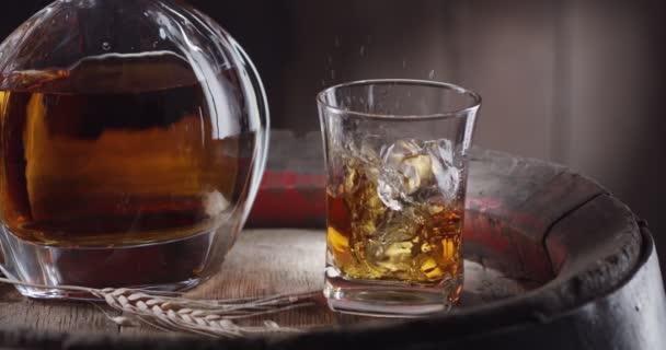 Egy jégkocka lassan beleesik egy pohár whiskybe egy régi whiskey hordó tetején. Egy korsó ital áll a közelben, sötét barna háttér. Fekete mágia Ursa Pro G2.