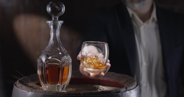Muž v obleku a vousu (sommelier) si vezme sklenici whisky na led ze starého sudu whisky a třese sklenicí, aby rozšířil vůni whisky. Zpomalení 4K, 150 fps, Blackmagic Ursa Pro G2.