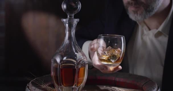 Mann in Anzug und Bart (Sommelier) nimmt ein Glas Whisky auf Eis aus einem Whisky-Vintage-Fass und schüttelt das Glas, um den Geruch von Whisky zu verbreiten. Zeitlupe 4K, 150 fps, Blackmagic Ursa Pro G2.