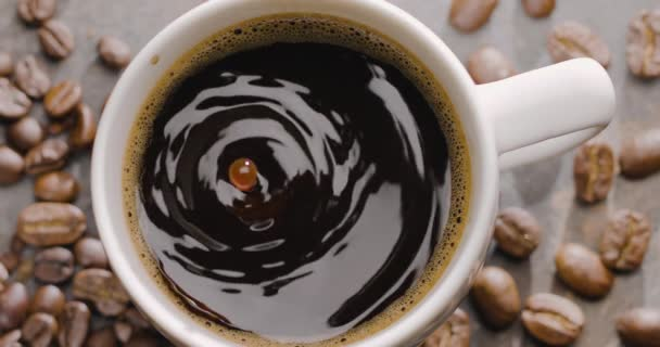 Drop of coffee slowly falls into a cup with coffee, top view, close-up, 300fps, Blackmagic Ursa Pro G2.