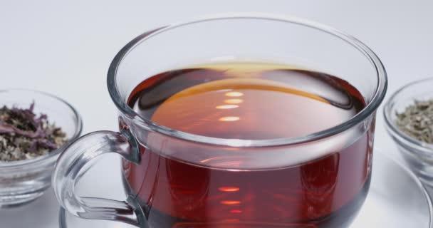 Kapka pomalu padá do skleněného šálku čaje. Kolem jsou malé misky s různými druhy listového čaje. Bílé pozadí.