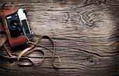 Starý dálkoměrný fotoaparát na starý dřevěný stůl