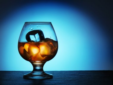Glass of whiskey with ice on a blue background.