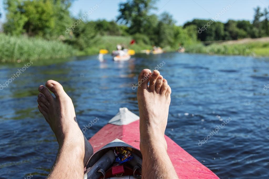 Man's legs over canoe.
