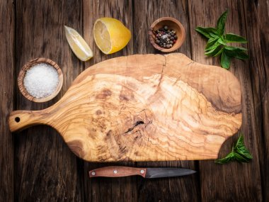 Olive cutting board and spices on a wooden table.