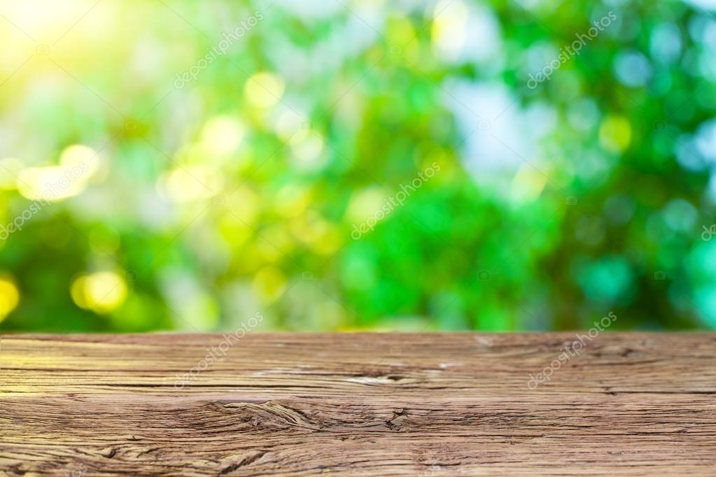Wooden desk and blurred foliage on the background.