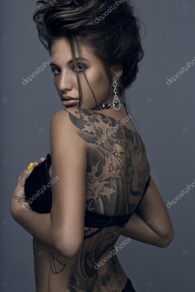 Sensual brunette woman with tattoo