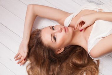 Sexy and Beautiful Woman with long Hair lying on the wooden floor