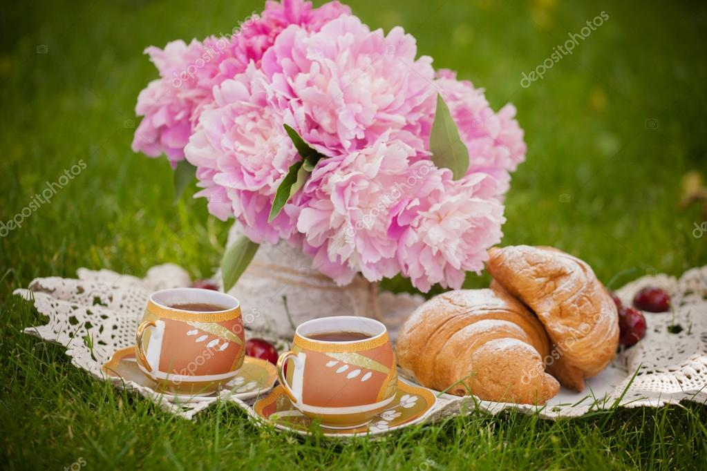 romantic breakfast in nature with fresh croissants and tea on a summer day