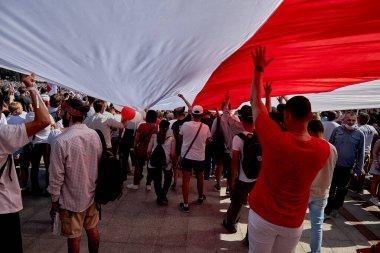 August 16 2020 Minsk Belarus Many people walk during a demonstration under a large opposition flag of Belarus