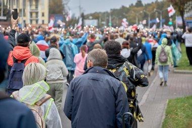 Bayrakları ve balonları olan, cep telefonlarında el fenerleriyle ellerini kaldıran bir kalabalık, protesto etmek için sokakta yürüyorlar.