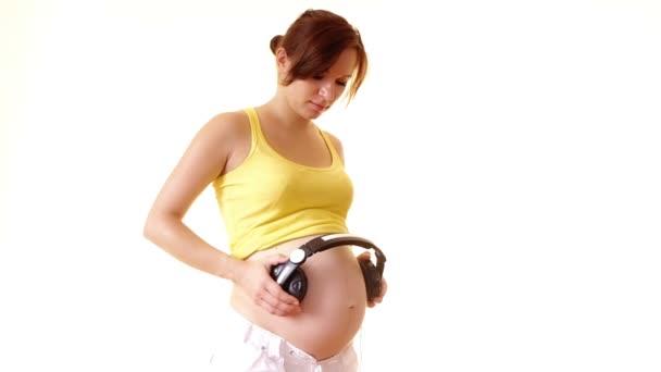 Sluchátka na její těhotné břicho