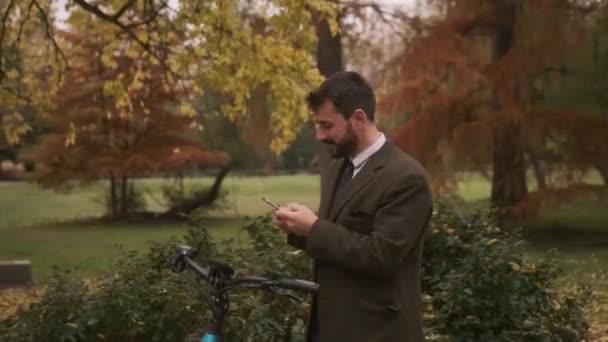 Schöner junger Mann mit Elektrofahrrad und Handy im Herbstpark
