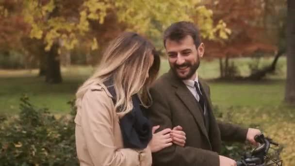 Schönes junges Paar im Herbstpark mit Elektrofahrrad
