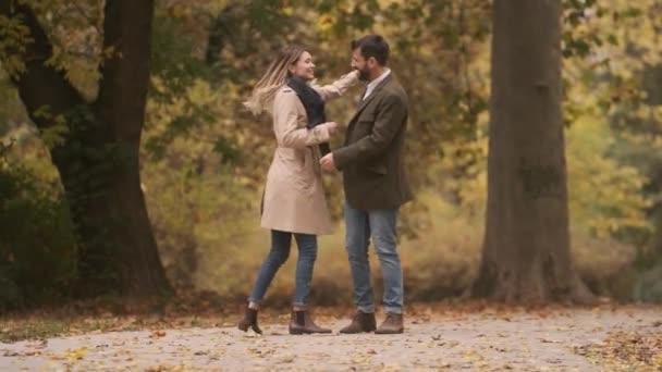 Jóképű fiatal pár sétál az őszi parkban