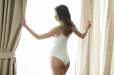 Girl posing in underwear by the window