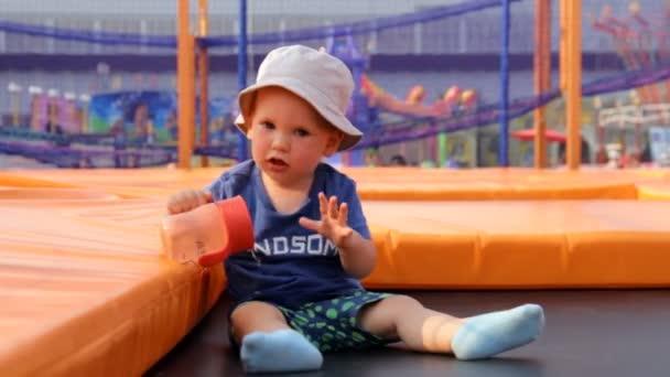 das Kind sitzt auf einem Trampolin und trinkt Wasser aus einer Flasche