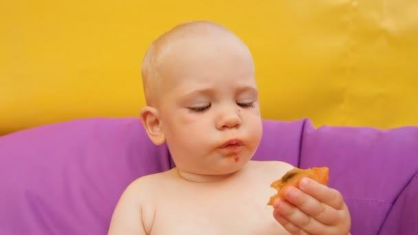 Dítě jíst ovoce, ležící v křesle