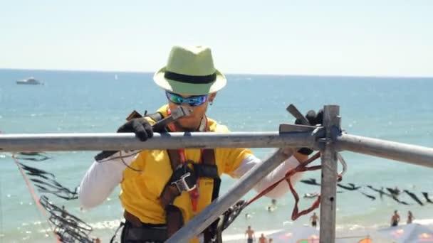 Muž v rámci oprav lešení bije kladivo
