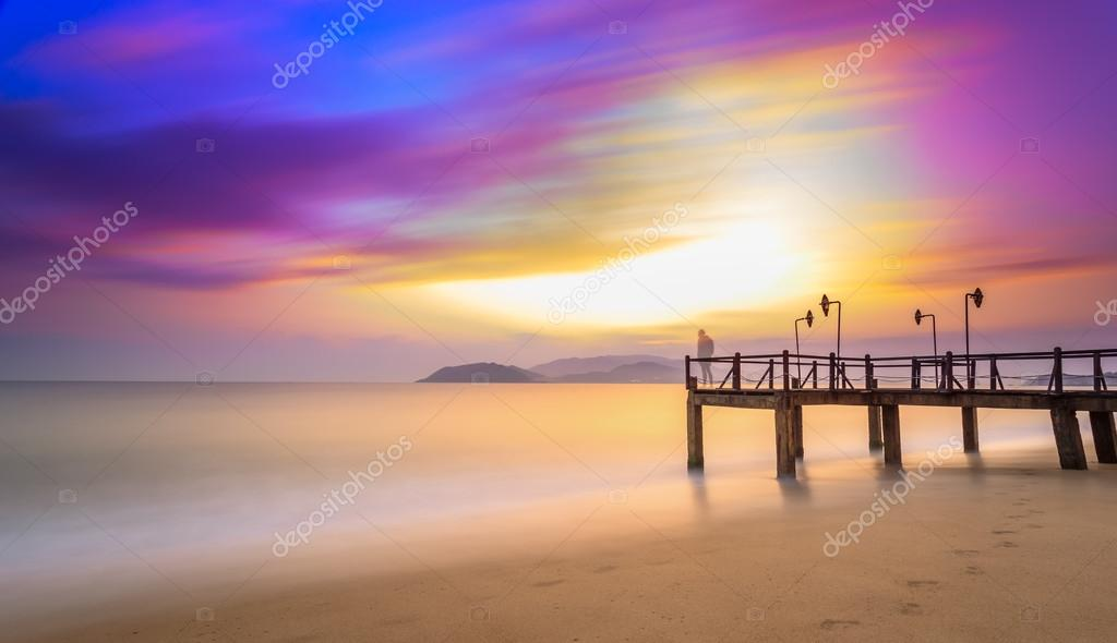 Long exposure of colorful sunrise and wooden pier