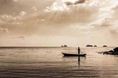 silhouette of Fisherman controls the Fishing boat. sepia toned