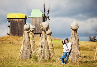 Young couple in Ukrainian style clothing kissing on field with bundles of straw and old windmills in background