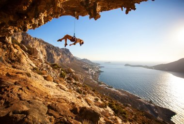 Female rock climber hanging on rope after unsuccessful attempt to take next handhold on cliff while lead climbing