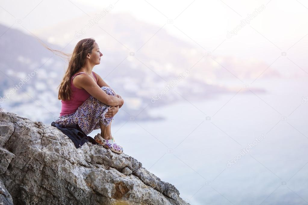 Young woman sitting on rock