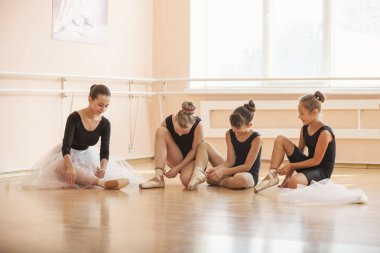 Young ballerinas putting on pointe shoes while sitting on floor in ballet class